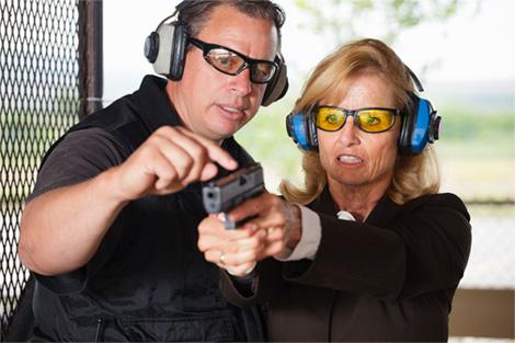 Man teaching a woman how to shoot